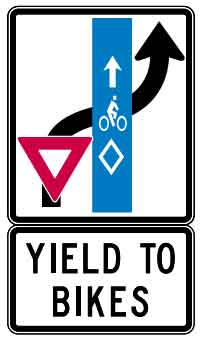 Sign showing the car turning right and entering the right turn lane to yield to the bicycles in the bike lane.